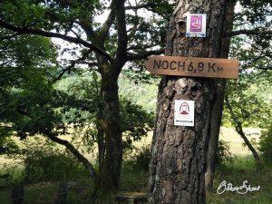 """Schild mit """"Noch 6,8 Km"""": Manchmal muss man zusätzliche Kilometer in Kauf nehmen, wenn es Engpässe gibt bei Unterkunft und Verpflegung."""