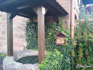 Brunnen und Stempelkästchen am Ortseingang Mernes.