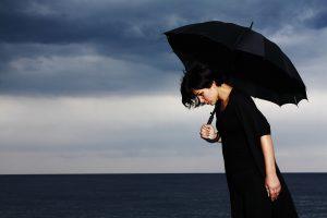 Gebeugte Frau mit schwarzem Regenschirm. Bild von Engin Akyurt auf Pixabay